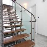 Escalier design avec poutre centrale marches en bois et garde corps à paroie vitrée EDI44
